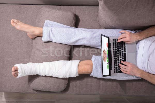 Man With Plastered Leg Using Laptop Stock photo © AndreyPopov