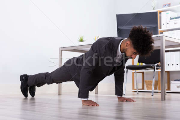 Businessman Doing Push Up In Office Stock photo © AndreyPopov