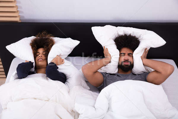 Young Couple Covering Their Ears With Pillow Stock photo © AndreyPopov