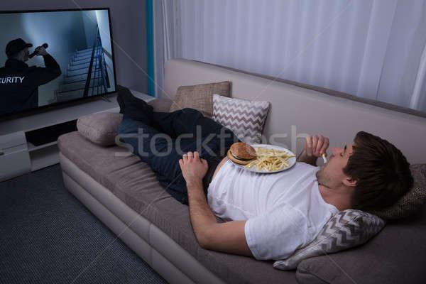 Homme manger frites françaises Burger jeune homme canapé Photo stock © AndreyPopov