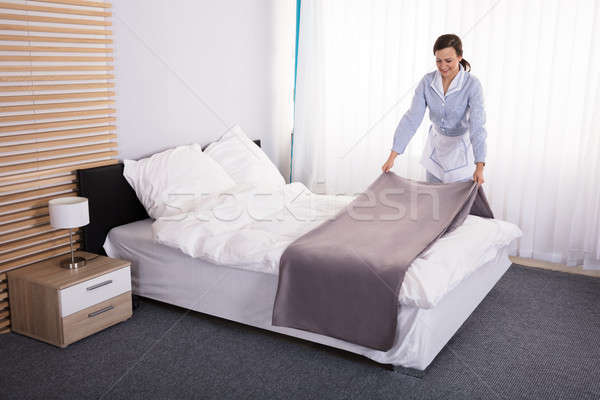 Governanta cama quarto de hotel sorridente feminino Foto stock © AndreyPopov
