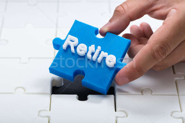 Person placing last retire piece into jigsaw puzzle Stock photo © AndreyPopov