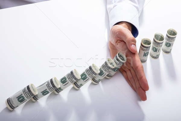 Person Stopping Falling Banknotes On Desk Stock photo © AndreyPopov