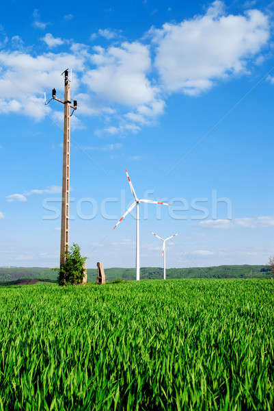Wind energy turbines and old transmission tower on the field Stock photo © Anettphoto