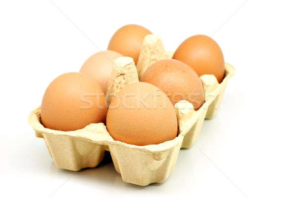 Half carton of eggs over white Stock photo © Anettphoto
