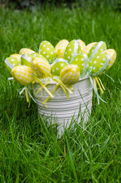 Easter eggs in white pail on grass Stock photo © anmalkov