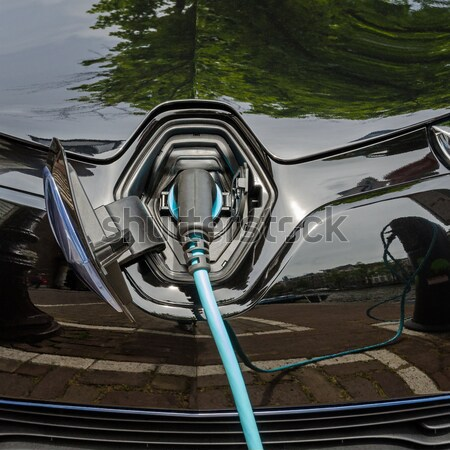 Charging modern electric car with power supply plugged in Stock photo © anmalkov