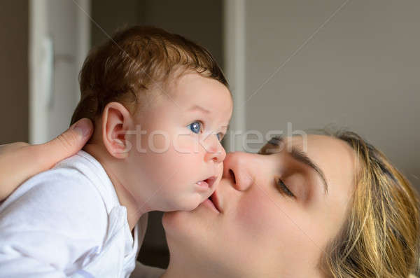 Young mother kissing her adorable baby boy Stock photo © anmalkov