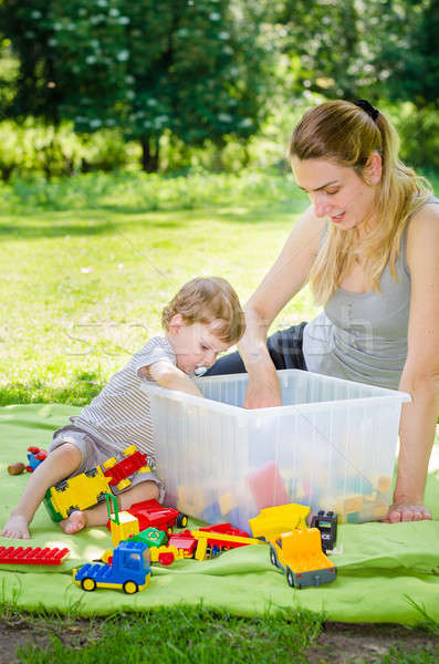 Cute baby boy plays toys with young mother in park Stock photo © anmalkov