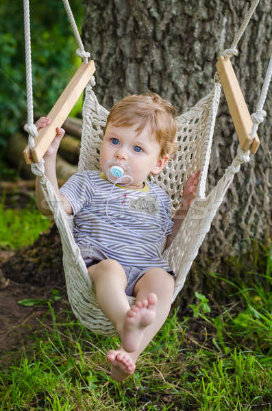 Little cute baby boy riding on hammock swing at park Stock photo © anmalkov