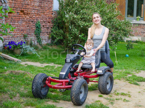 Little cute boy driving pedal car with young mother Stock photo © anmalkov