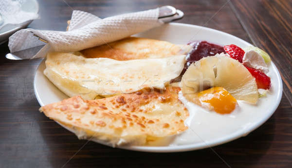 Pancakes on white plate and dark background with cream, strawber Stock photo © anmalkov