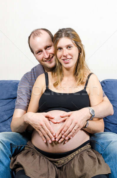 Stock photo: Happy parents make heart sign on pregnant woman's belly on couch