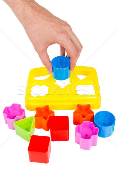 Human hand puts wrong shape into shape sorter toy isolated Stock photo © anmalkov