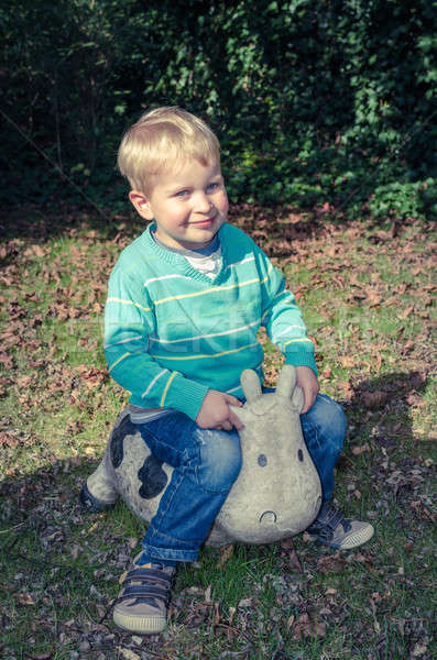 Young cute little boy sitting on toy cow outside Stock photo © anmalkov