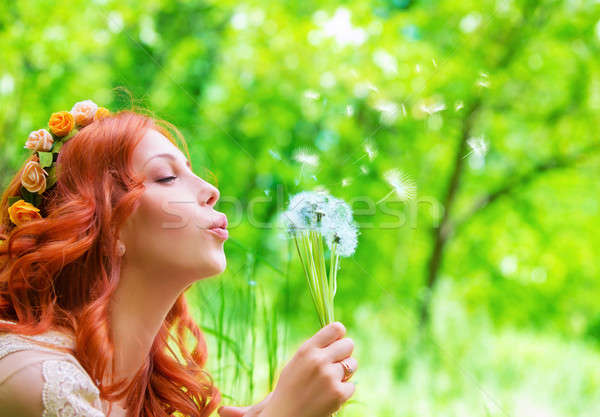 Stock photo: Pretty woman blowing on dandelion