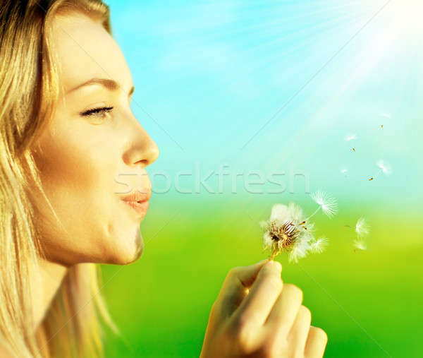 Stock photo: Happy beautiful girl blowing dandelion