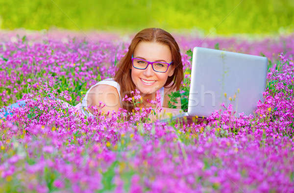 Pretty woman with laptop on floral field Stock photo © Anna_Om
