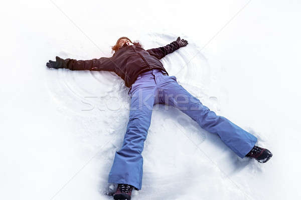 Young female making snow angel Stock photo © Anna_Om