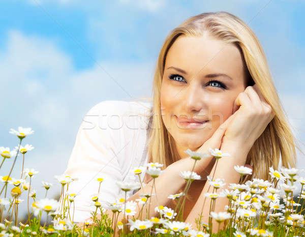Stock photo: Beautiful woman enjoying daisy field and blue sky