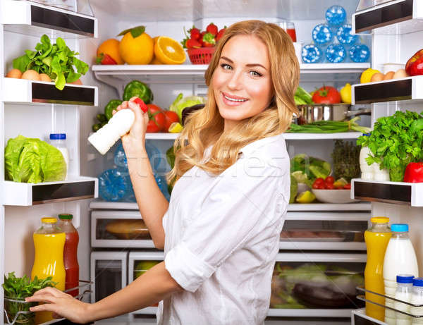 Woman chosen milk in opened refrigerator Stock photo © Anna_Om