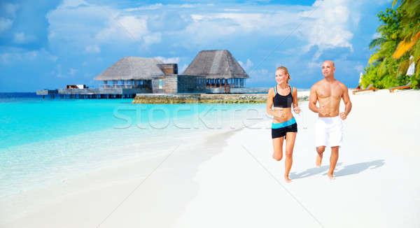 Happy couple jogging on the beach Stock photo © Anna_Om