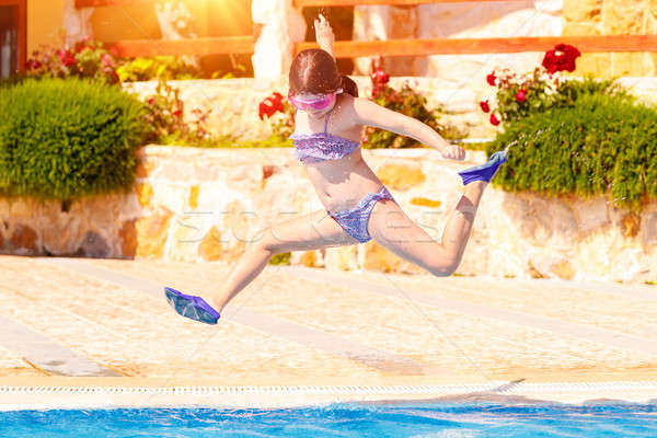Stock photo: Happy girl jumping to the pool