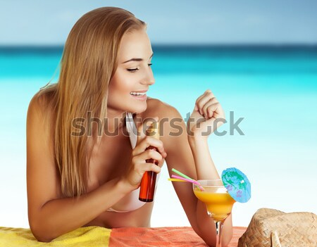 Woman with cocktail and sunblock on the beach Stock photo © Anna_Om