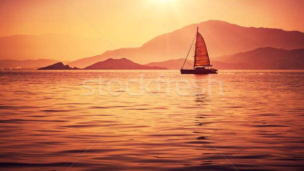 Zeilboot mooie zonsondergang licht oranje zeil Stockfoto © Anna_Om