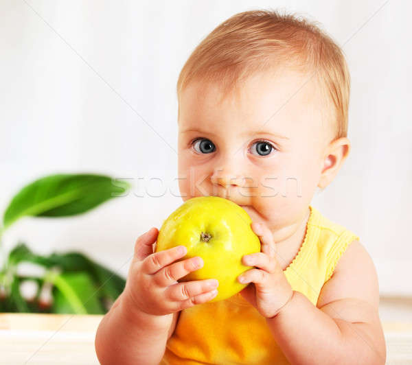 Stock photo: Little baby eating apple