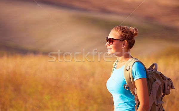 Beautiful traveler girl enjoying golden wheat field in sunset light, beautiful summer nature, farmla Stock photo © Anna_Om