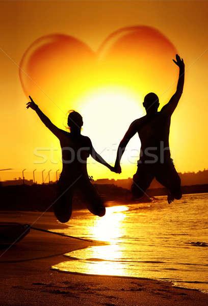 Stock fotó: Szeretet · boldog · fiatal · pér · ugrik · kéz · a · kézben · szív · alak