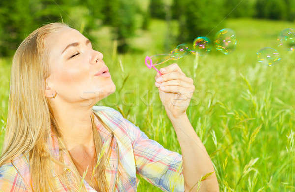 Pretty woman blowing soap bubbles in park Stock photo © Anna_Om