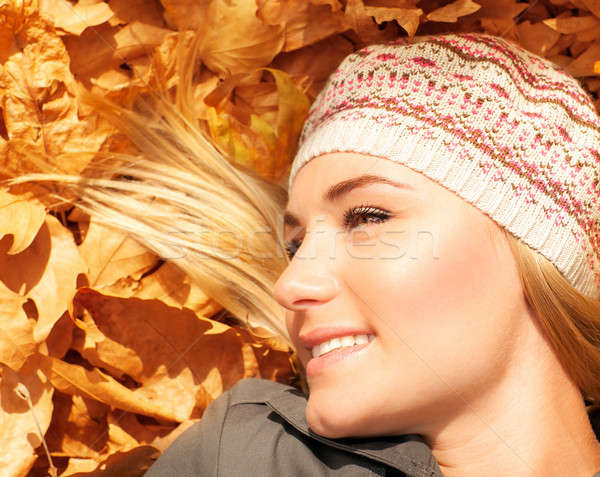 Cute blonde laying down on tree leaves Stock photo © Anna_Om