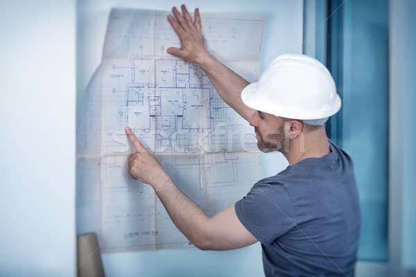 Architect builder studying layout plan of the rooms Stock photo © Anna_Om