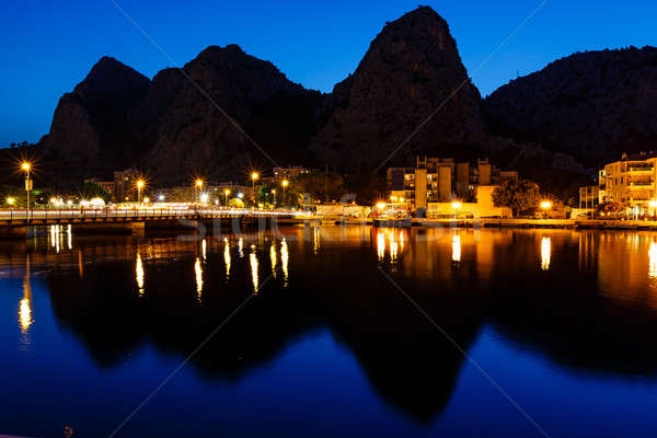 Mountain Silhouettes and Illuminated Town of Omis Reflecting in  Stock photo © anshar