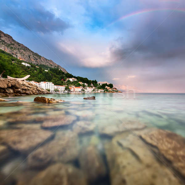 Rainbow over Rocky Beach and Small Village after the Rain, Dalma Stock photo © anshar