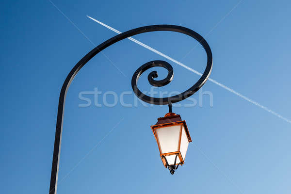 Shining Backlit Streetlamp and Airplane Trail in Background, Meg Stock photo © anshar