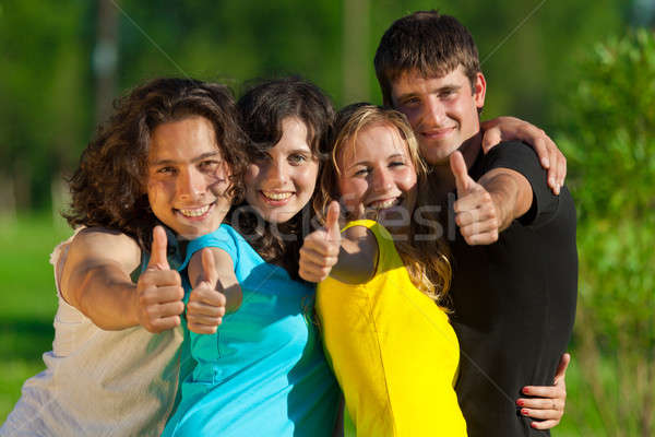 Young group of happy friends showing thumbs up sign Stock photo © Antartis