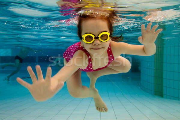 The girl smiles, swimming under water in the pool Stock photo © Antartis