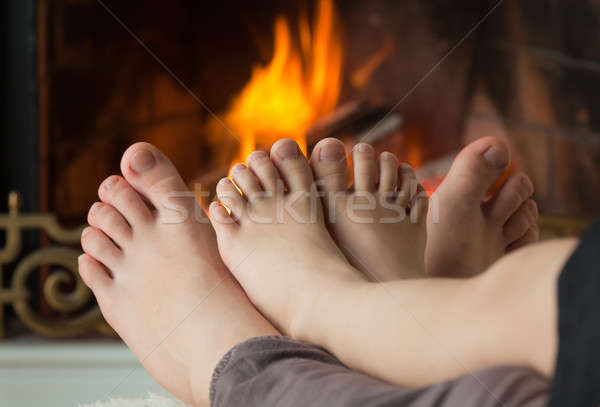 Children's feet are heated by an open fire in the fireplace Stock photo © Antartis
