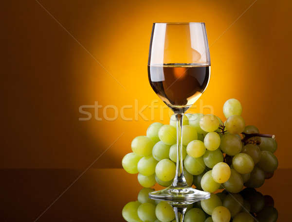 A glass of white wine and a bunch of green grapes Stock photo © Antartis