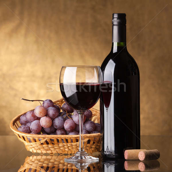 Stock photo: A bottle of red wine, glass and grapes