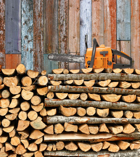 Stacked firewood with chain saw Stock photo © Anterovium