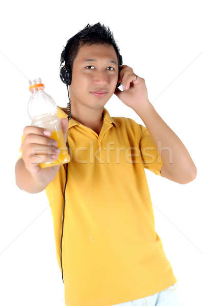 young man listening to music while brandishing his drink bottle Stock photo © antonihalim