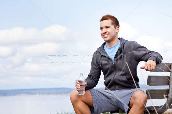 Mixed race man holding water bottle Stock photo © aremafoto