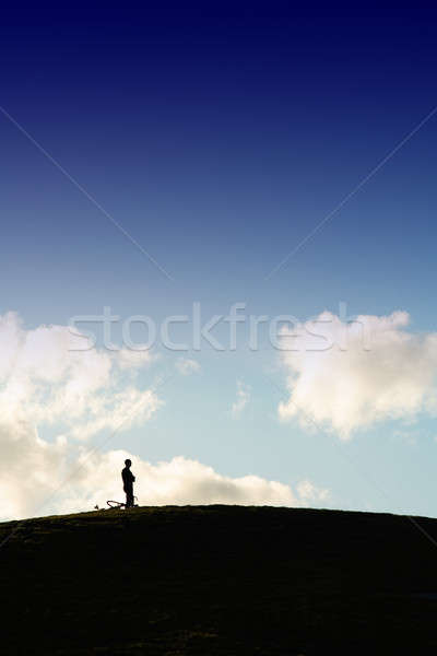 Solitude silhouette homme permanent haut colline Photo stock © aremafoto