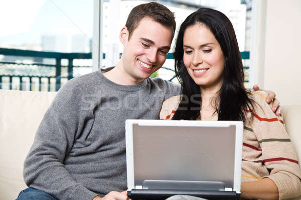 Happy couple browsing internet at home Stock photo © aremafoto