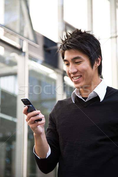 Sms chat lezser ázsiai üzletember üzenetek mobiltelefon Stock fotó © aremafoto