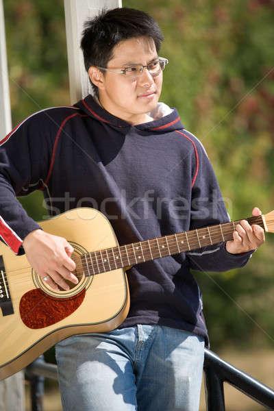 Young asian guitar player Stock photo © aremafoto
